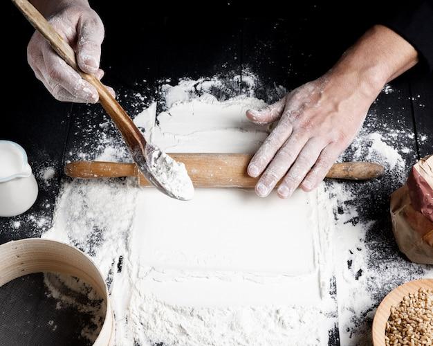 Rouleau à pâtisserie en bois dans les mains des hommes