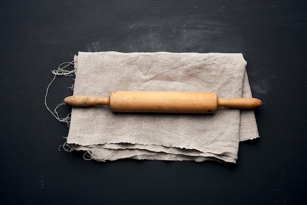 Rouleau à pâtisserie en bois se trouvent sur une serviette en lin gris, table noire