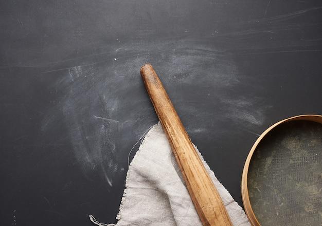 Rouleau à pâtisserie en bois et un tamis rond reposent sur une serviette en lin gris, table noire
