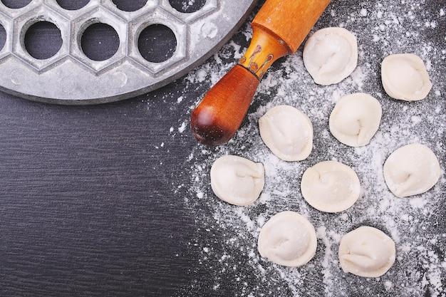Rouleau à pâtisserie, boulettes crues dans la farine sur un fond noir.