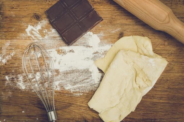 Rouleau à pâtisserie, chocolat, farine et pâte allongé sur planche de bois