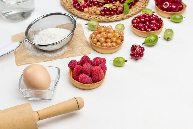 Rouleau à pâtisserie et œuf, bouteille d'eau. farine au tamis. tartelettes aux fruits rouges. groseilles rouges sur plaque en osier. espace de copie. fond blanc. vue de dessus