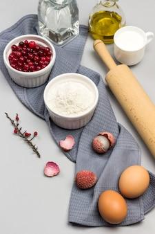Rouleau à pâtisserie, oeufs et bol de farine sur une serviette grise. bol de canneberges. fouet en métal, deux bouteilles d'eau et d'huile. vue de dessus.