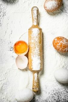Rouleau à pâtisserie avec des œufs frais sur farine.