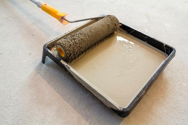 Rouleau à peinture dans le bac à peinture avec la couleur grise dans le bac