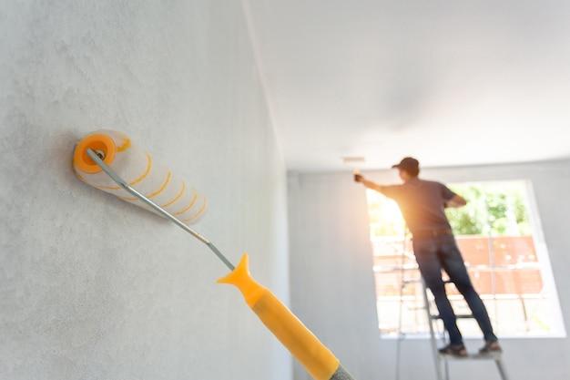Rouleau de peinture intérieure et le travailleur en arrière-plan. concept de rénovation de maison.