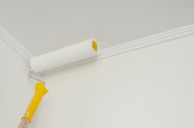 Rouleau à peinture avec manche jaune.