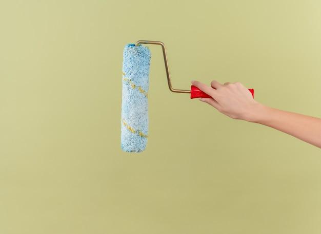 Rouleau à peinture sur mur vert isolé