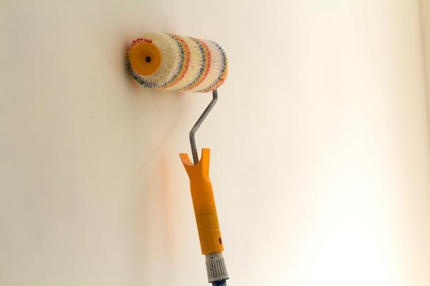 Rouleau à peinture près du mur à l'intérieur de la pièce rénovée isolé sur une surface blanche. concept de rénovation et de bricolage.