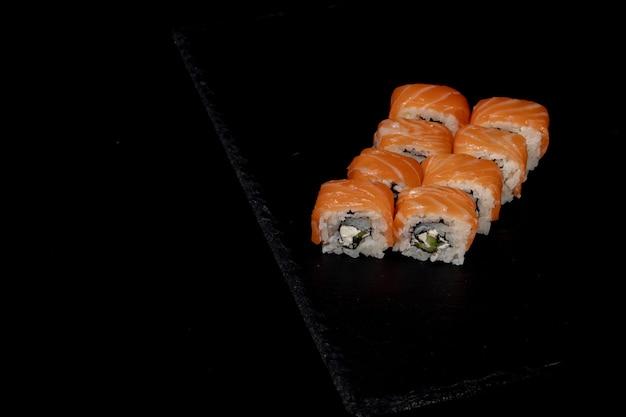 Rouleau de philadelphie avec saumon, fromage et concombre sur fond noir. sushi philadelphie