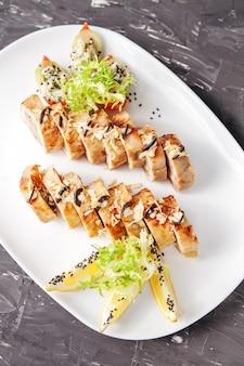 Rouleau de poulet aux champignons farcis sur une assiette blanche. backg gris foncé
