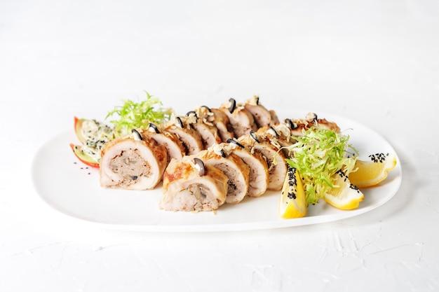 Rouleau de poulet aux champignons farcis sur une assiette blanche. le concept de