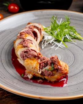 Rouleau de poulet farci à la viande et servi avec des légumes verts