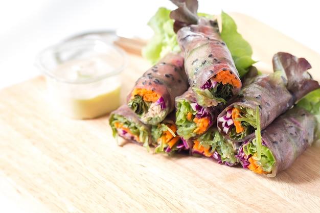 Rouleau de printemps frais ou rouleau à salade mélangé avec du thon à la carotte légume sur planche à découper.
