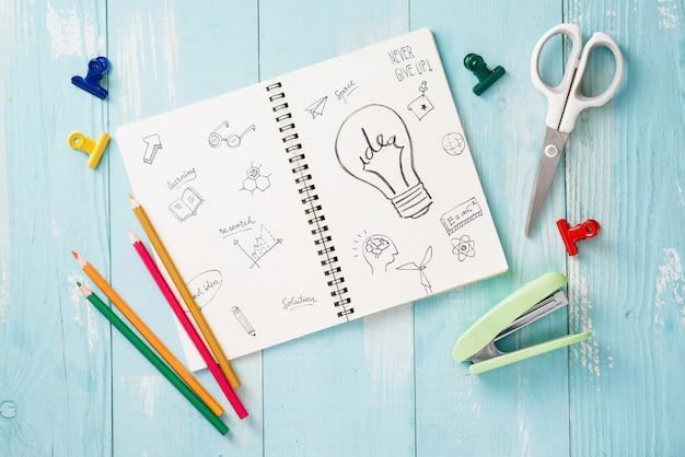 Rouleau de ruban adhésif en papier, trombones et blocs-notes posés sur une table en bois, fournitures scolaires, fournitures de bureau, retour à l'école
