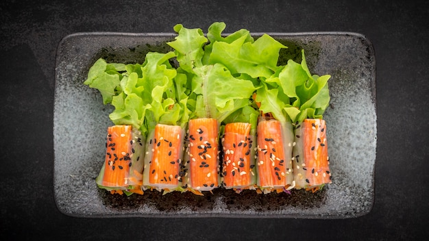 Rouleau de salade de bâtonnets de crabe imitation avec mélange de légumes biologiques garni de sésame sur fond de texture de ton sombre, vue de dessus, nourriture saine, rapport full hd