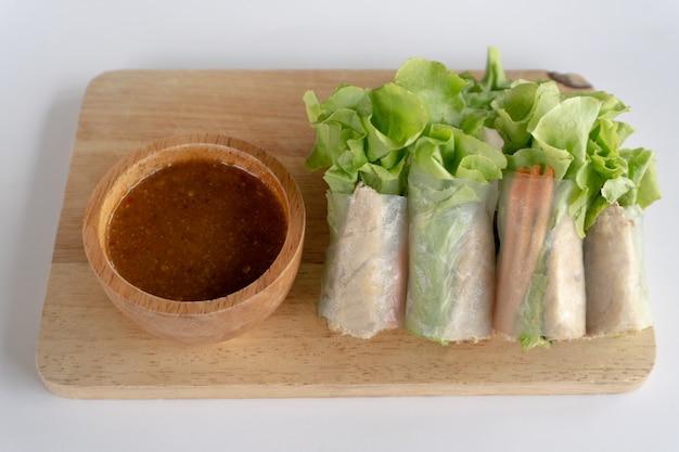 Rouleau de salade de maquereau sur une planche à découper et sauce aux fruits de mer sur un bol en bois, le rouleau de salade est une cuisine de rue populaire en thaïlande et une bonne nourriture pour l'alimentation.