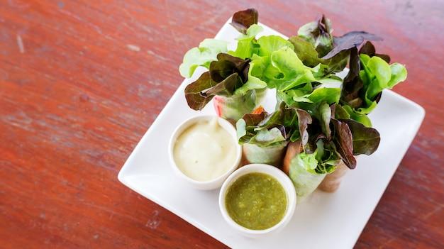 Rouleau de salade et vinaigrette sur une assiette blanche.