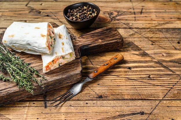 Rouleau de sandwich au shawarma de lavash, poulet, boeuf, champignons, fromage. fond en bois. vue de dessus. copiez l'espace.