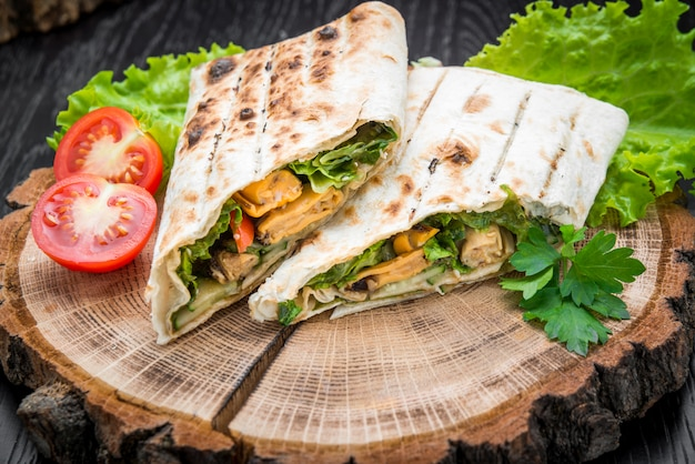 Rouleau de sandwich avec des bâtonnets de poisson, du fromage et des légumes sur la table
