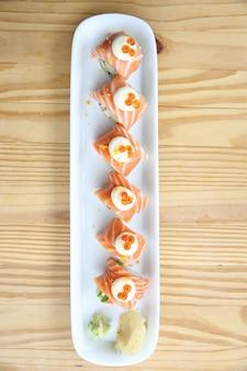 Rouleau de saumon de cuisine japonaise sur fond de bois