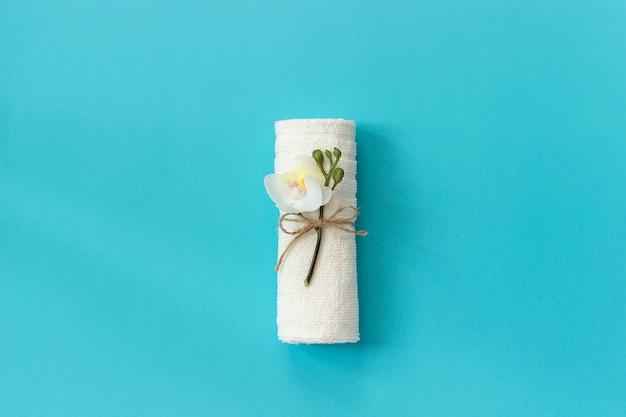Rouleau de serviette blanche attachée avec une corde avec un brin de fleur d'orchidée sur fond de papier bleu.