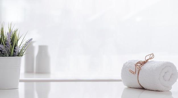 Rouleau de serviette de spa blanc attaché avec une corde de chanvre sur une table de comptoir blanche