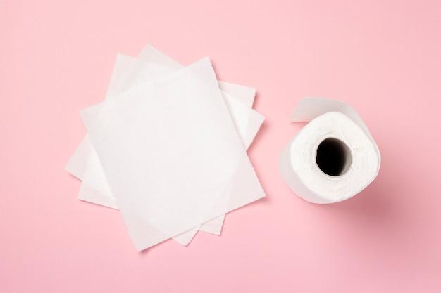 Rouleau de serviettes en papier et quelques morceaux de serviettes sur fond rose. le concept est un produit 100% naturel, délicat et doux. mise à plat, vue de dessus. bannière