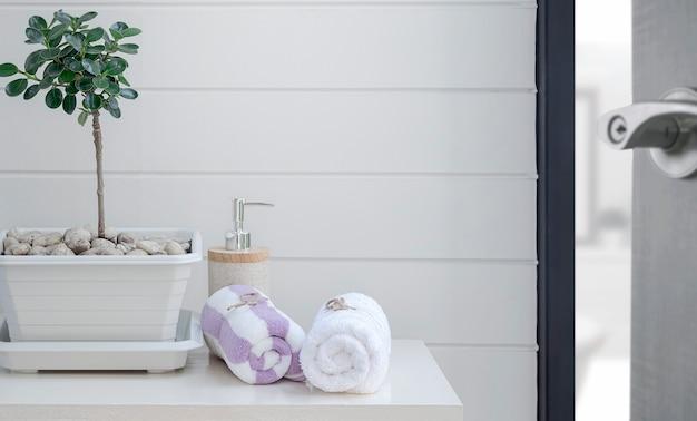 Rouleau de serviettes propres sur table blanche dans la salle de bain.