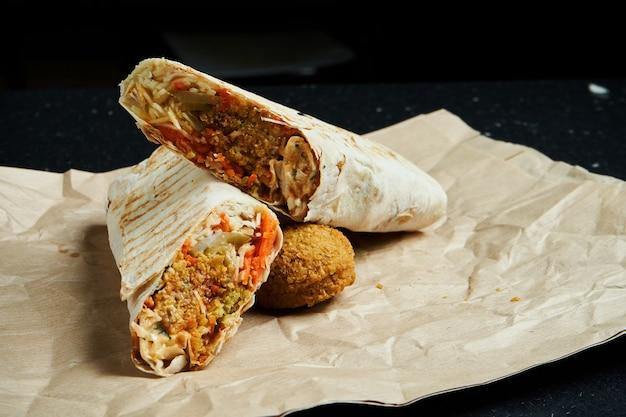 Rouleau de shawarma appétissant avec falafel, salade et sauce maison dans du pain pita fin sur du papier kraft sur une surface noire. cuisine orientale. kebab tranché avec falafel.