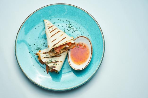 Rouleau de shawarma appétissant avec de la viande, de la salade et de la sauce maison dans du pain pita mince dans une assiette bleue isolée sur une surface grise. cuisine orientale. kebab en tranches avec de la viande grillée.