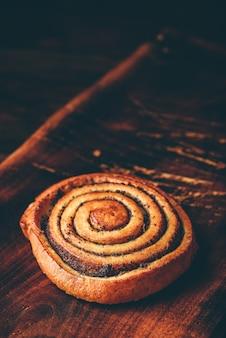 Rouleau sucré aux graines de pavot sur une surface en bois rustique