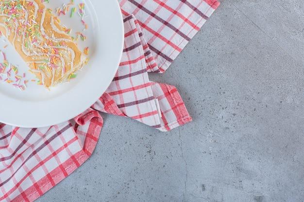 Rouleau sucré à saveur de vanille décoré de pépites sur plaque blanche.