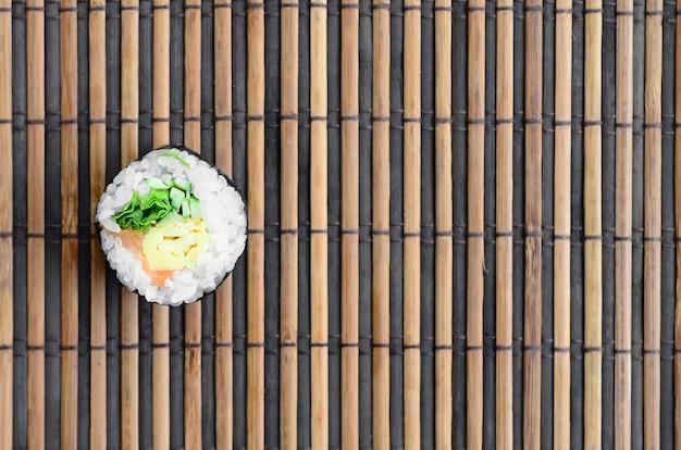 Rouleau de sushi allongé sur un tapis de serwing en paille de bambou