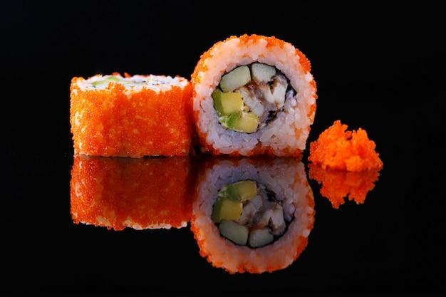 Rouleau de sushi appétissant avec poisson et caviar, sur fond noir avec reflet. menu et restaurant.