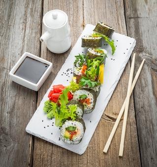 Rouleau de sushi au chou frisé et à l'avocat sain avec des baguettes. rouleaux végétariens