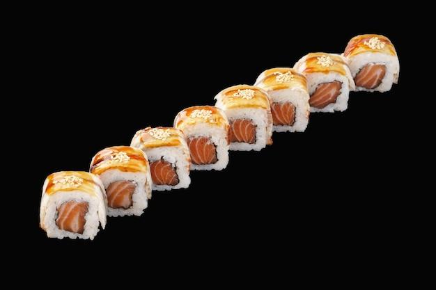Rouleau de sushi au saumon, anguille, mayonnaise japonaise, sauce unagi, sésame et pétoncle isolé sur noir