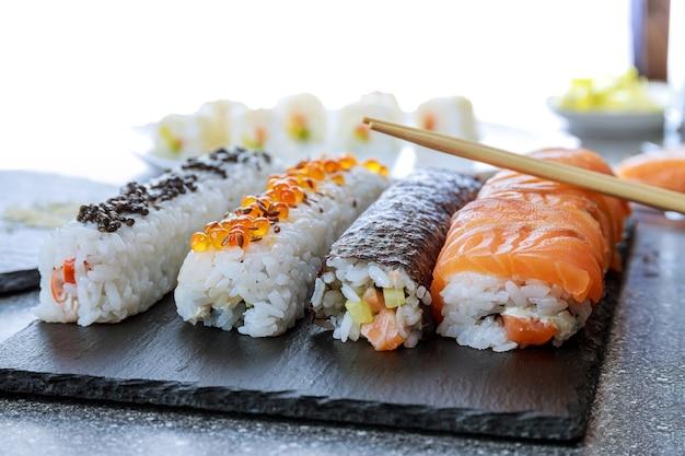 Rouleau de sushi au saumon, caviar rouge et caviar noir sur une plaque noire sur une surface en bois. femme à l'aide d'un tapis roulant en bambou pour des sushis faits maison