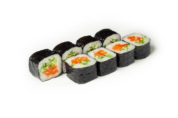 Rouleau de sushi au saumon et concombre sur une plaque blanche
