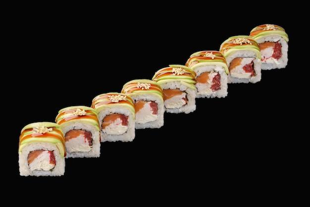 Rouleau de sushi au saumon, crabe des neiges, fromage philadelphia, avocat, tomate, sauce unagi, sésame isolé sur fond noir