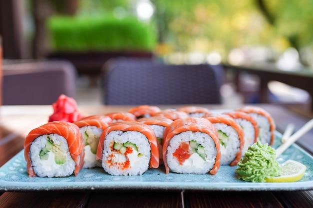 Rouleau de sushi au saumon et crevettes tempura sur plaque