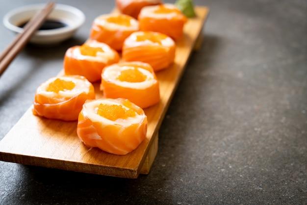 Rouleau de sushi au saumon frais avec mayonnaise et œuf de crevettes - style de cuisine japonaise