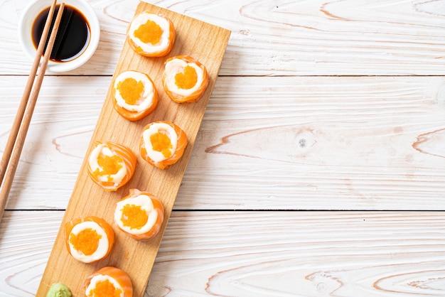 Rouleau de sushi au saumon frais avec mayonnaise et œuf de crevettes, style japonais