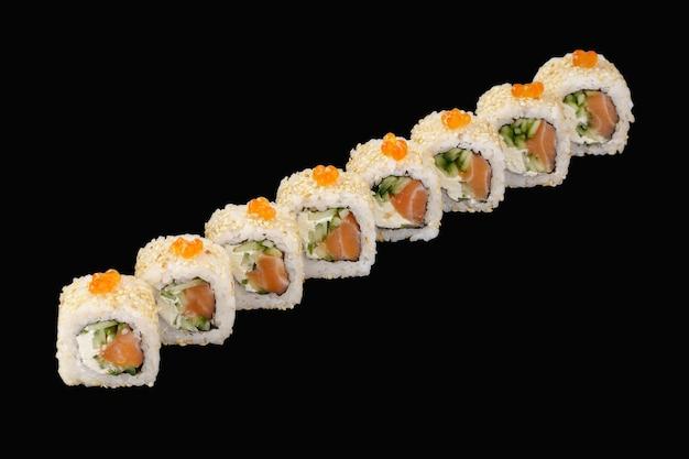 Rouleau de sushi au saumon, fromage philadelphia, caviar rouge, concombre, sésame isolé sur fond noir