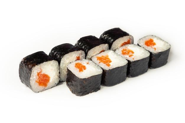 Rouleau de sushi au saumon et fromage sur une plaque blanche