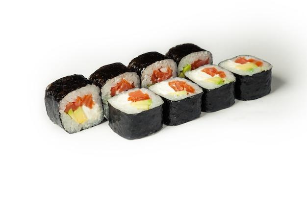 Rouleau de sushi au saumon fumé et avocat sur une plaque blanche