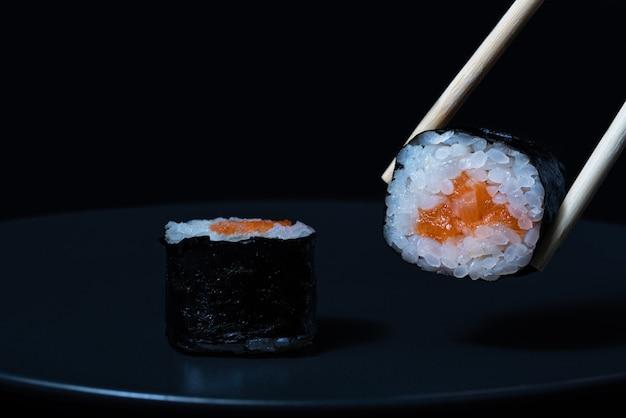 Rouleau de sushi au saumon sur une plaque noire en gros plan des baguettes en bois tiennent un rouleau de sushi