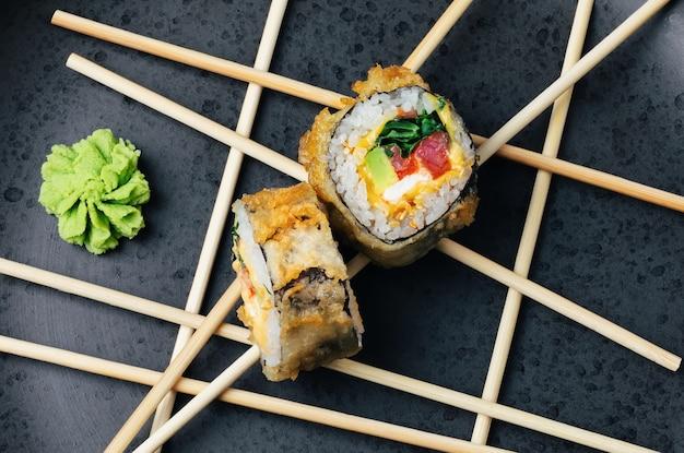 Rouleau de sushi au thon fait maison avec avocat et fromage dans une panure croustillante sur une assiette en pierre sombre.