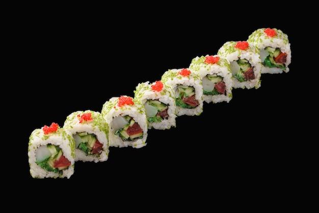 Rouleau de sushi aux pétoncles, caviar tobiko, chuka, tomate, concombre, mayonnaise japonaise, sésame isolé sur fond noir
