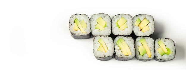 Rouleau de sushi à l'avocat sur une plaque blanche